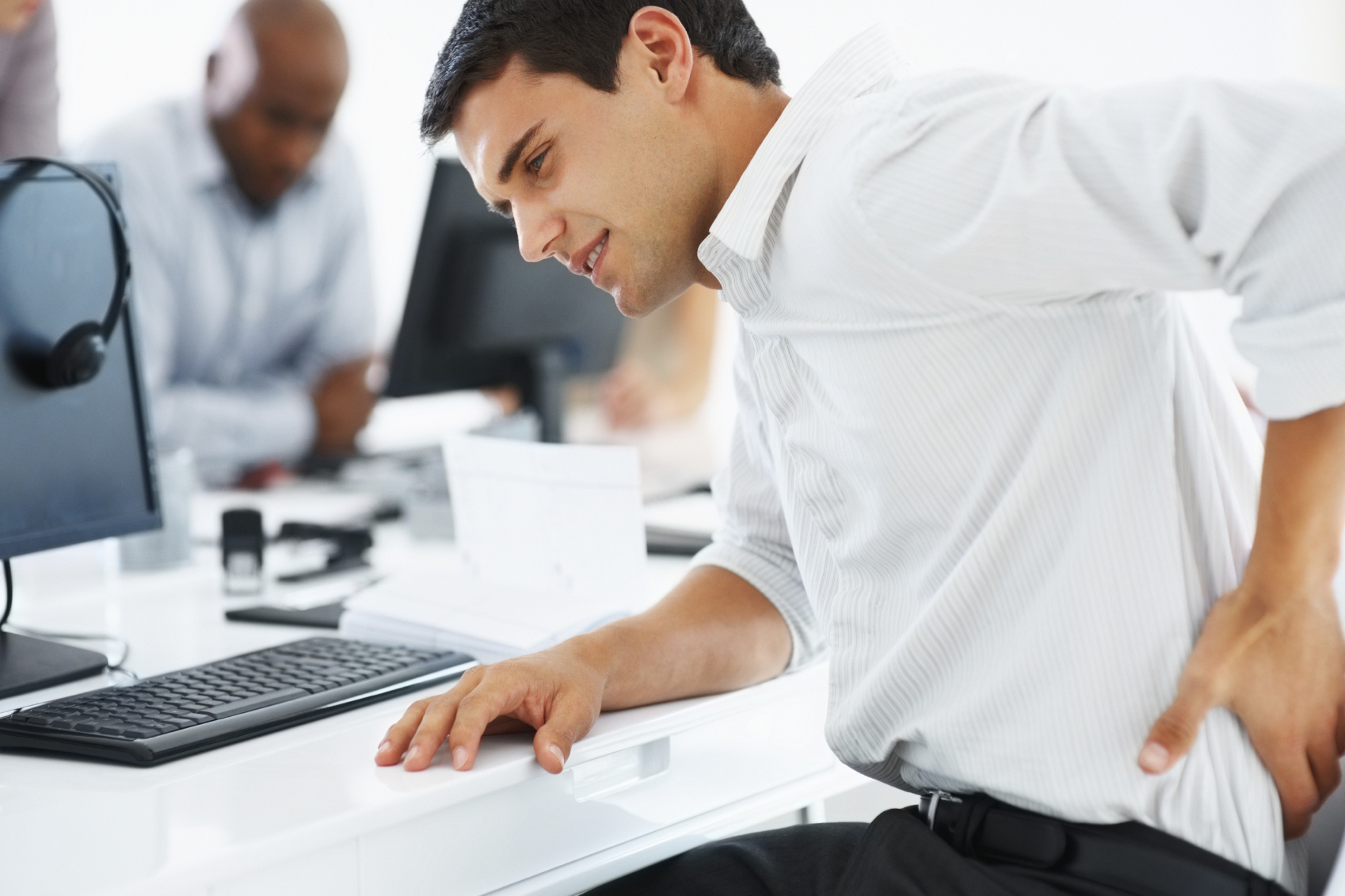 Young business man holding his lower back at work